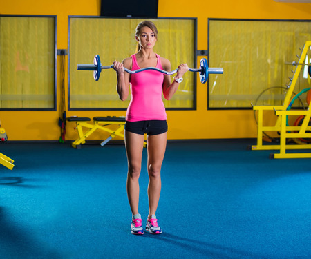 lifting weights: Woman in gym lifting weights