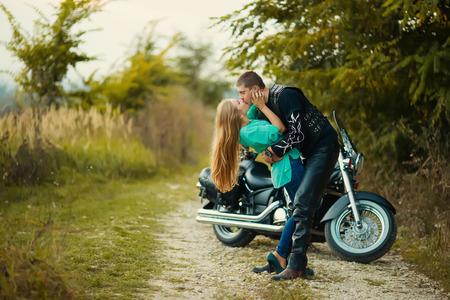 Young couple with beautiful bike on road. Standard-Bild