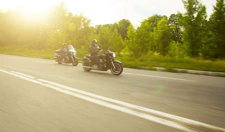 slow motion, two bikers riding unknown motorbike with blur movement, speed concept photo