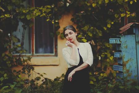 body toning: Melancholic woman in classic dress near old brick wall outdoor shot summer day. Toning photo