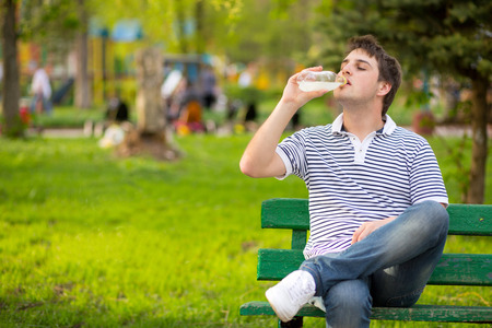 man drinking water: Young man drinking mineral water in green park Stock Photo