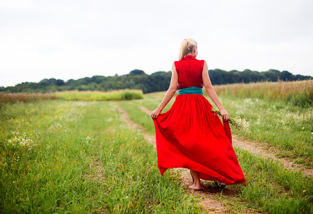 Beautiful young blonde woman in red dress in green field