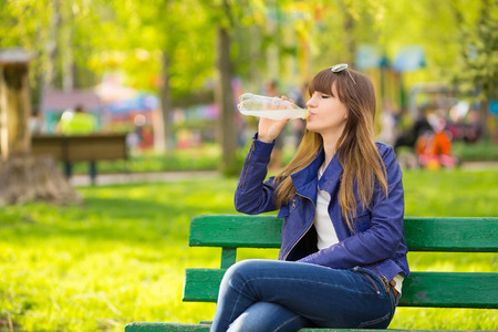 Beautiful Fashion Woman with handbag sitting and waiting on a bench in the park and drink water 版權商用圖片