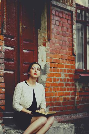 melancholijny: Melancholic woman in classic dress seat near old brick building and read book. Toning photo