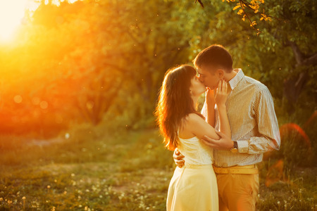 kissing couple: A young couple kiss in park at sunrise Stock Photo