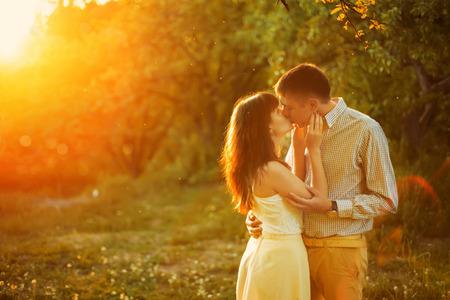personas besandose: Una joven pareja se besa en el parque en la salida del sol