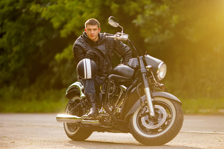 road bike: Smiling happy biker in sitting unknown on big chopper bike on road