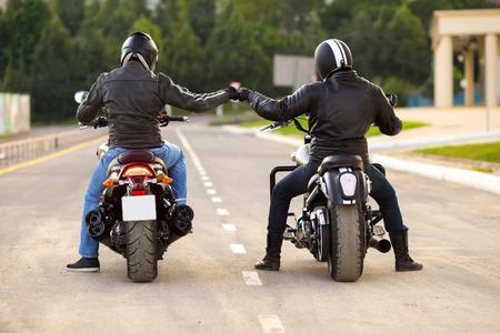 Dos motociclistas ot motocycles apretón de manos con nudillo en la carretera