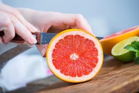 若いきれいなシェフ手カット グレープ フルーツ キッチンで古い木製のテーブルの上