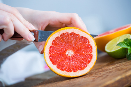 young clean chef hands cutting grapefruit on old wooden table in kitchen Reklamní fotografie