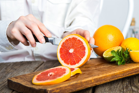 young clean chef hands cutting grapefruit on old wooden table in kitchen Stock Photo