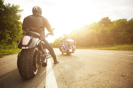 two bikers riding unknown motorbike with blur movement, speed concept Standard-Bild