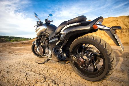 Big, clean, black and unknown chopper bike in desert Stock Photo
