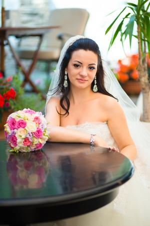 Foto von einer schönen Brünette Braut in einem luxuriösen Brautkleid im eleganten teuren Interieur