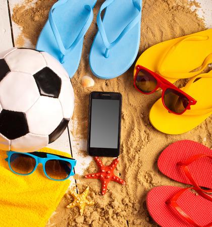 flip flops: Flip flops, ball, phone, seashell and starfish with tropical flowers on sandy beach Stock Photo