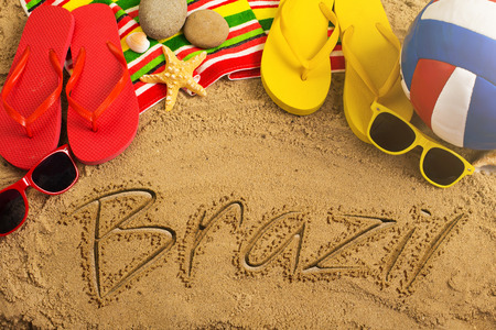 voyage: Summer concept of sandy beach, colorful thongs shoes, sunglasses, ball and inscription