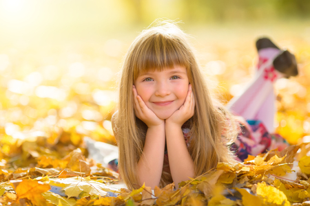 Little smiling girl with leaf resting on meadow in autumn park