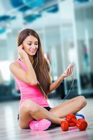 Lächelnde athletische Frau sitzen und mit Kopfhörern in einer Eignungmitte ausbilden