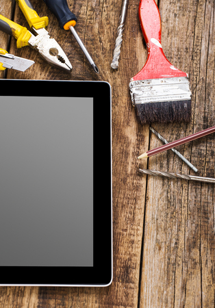 Different equipment tools of builder and tablet pc on wooden texture table Stock Photo