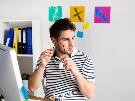 Young Handsome Graphic designer using graphics tablet to do his work at desk Stock Photo