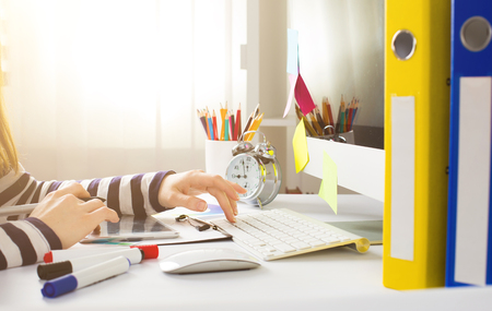 Young woman graphic designer using graphics tablet to do his work at desk