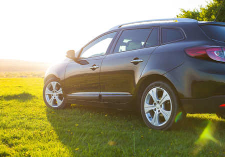 The unknown vehicle car on the grass in field at summer sunset Stockfoto