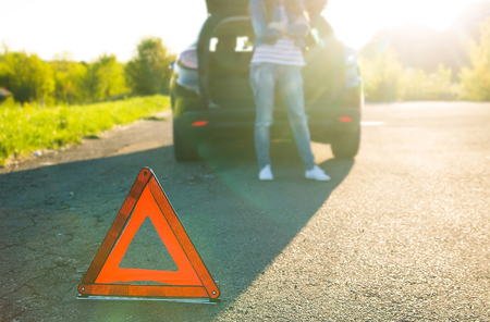 Car with problems and a red triangle to warn other road users