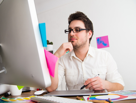 Young Handsome Graphic designer using graphic tablet to do his work at desk