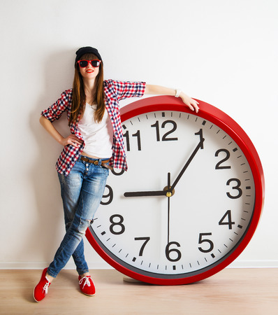 young woman with hat and glasses holding a clock. time management concept. nine o`clock Archivio Fotografico