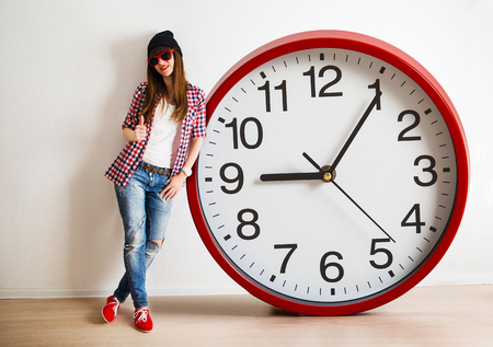 young woman with hat and glasses holding a clock. time management concept. nine o`clock Stock Photo