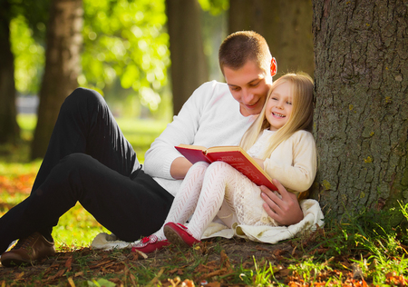 Cute little blonde girl sit near tree with father, read favorite book and dream
