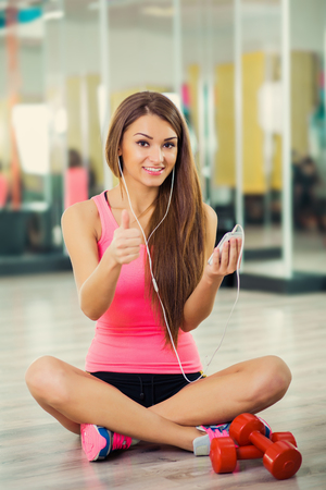 Smiling athletic woman sit and training with earphones in a fitness center Stock Photo