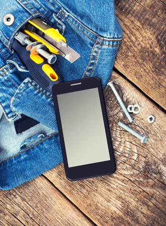 Tools, mobile smartphone, screwdriver, screw, stationary knife in blue jeans jacket pocket on wooden background