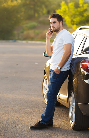 Car and smartphone app concept - man texting sms on phone. Driving young male adult using apps for travel or gps navigation help or reading news and texts using internet
