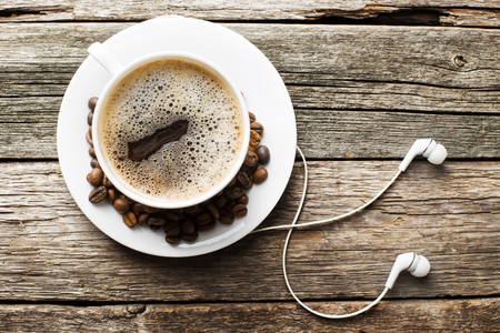 Headphones and coffee cup on wooden desk table. Music concept. Top view with copy space Stockfoto