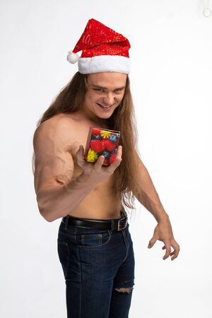 athlete bodybuilder shirtless with long hair posing in cap Santa Claus on a white background