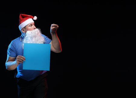 portrait actor male in cap and beard of Santa Claus with a sheet of paper for notes in the hands on a black background Stock Photo