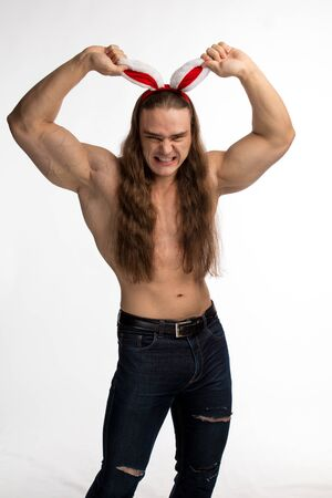 athlete bodybuilder shirtless with long hair posing with a rabbit-like ears on a white background