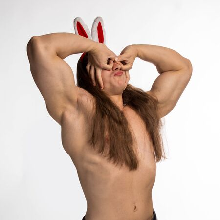 athlete bodybuilder shirtless with long hair posing with a rabbit-like ears on a white background 版權商用圖片