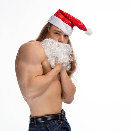 athlete bodybuilder shirtless with long hair posing with a beard and a cap of Santa Claus on a white background Stock Photo
