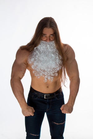 athlete bodybuilder shirtless with long hair posing in the beard of Santa Claus on a white background