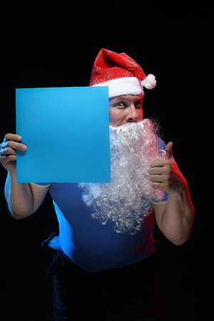 pere noel sexy: portrait actor male in cap and beard of Santa Claus with a sheet of paper for notes in the hands on a black background Banque d'images
