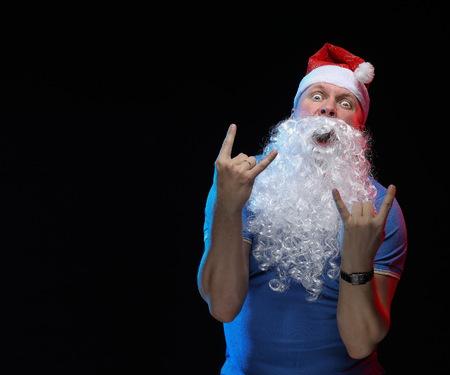 pere noel sexy: Acteur portrait mâle au chapeau et à la barbe du père Noël sur un fond noir