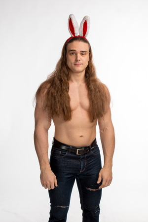 athlete bodybuilder shirtless with long hair posing with a rabbit-like ears on a white background Stock Photo