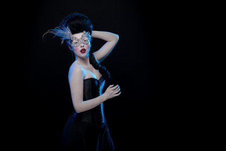 dark elf: brunette woman with high hair, a mask with feathers and corset in old style on a black background