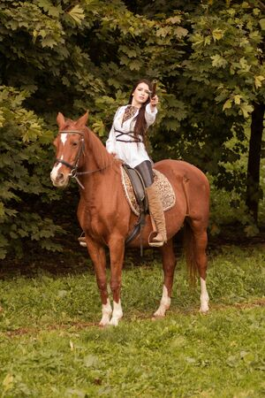 Young brunette woman with long hair posing with a brown red horse in a forest in a sunny meadow 写真素材