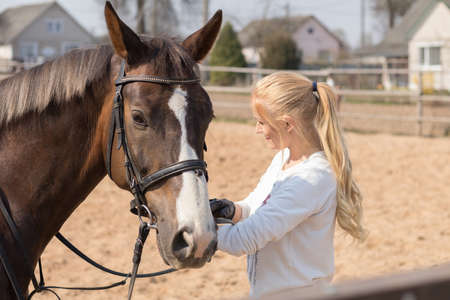 Girl riding a horse gallops in a paddock on a ranch