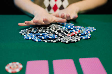 Female hands lay out playing cards and chips in a casino on a green table