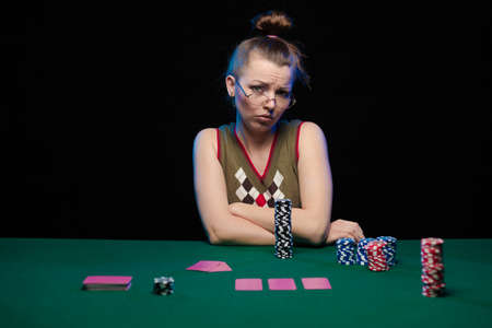 Emotional young girl with glasses playing cards on a table on green cloth at a casino