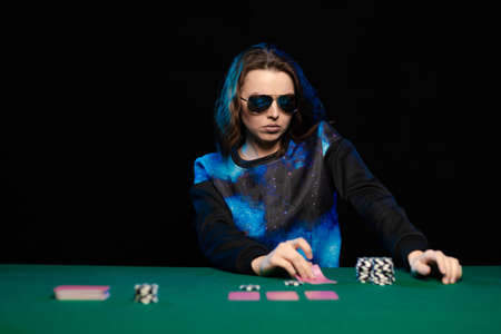 woman in blue clothes and sunglasses is playing cards in a casino on green cloth on a table